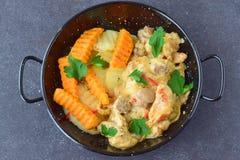 鸡内圆角用在一乳脂状的souce的蘑菇和在一个黑金属碗的油煎的白薯在一个灰色摘要 库存照片