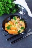 鸡内圆角用在一乳脂状的souce的蘑菇和在一个黑金属碗的油煎的白薯在一个灰色摘要 库存图片