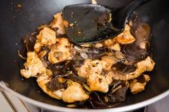 鸡和木头耳朵在铁锅的蘑菇盘 免版税库存图片