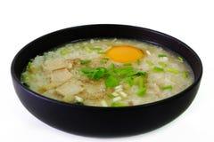 鸡和鸡蛋用煮沸的米在黑碗在白色背景 免版税库存图片