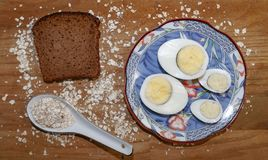 鸡和鹌鹑蛋在一个蓝色茶碟和燕麦芯片和黑面包片断  免版税库存照片