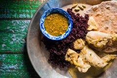 鸡咖喱和面包薄煎饼在一个木立场 印第安盘 免版税库存照片