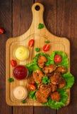 鸡块和调味汁在木背景 库存照片