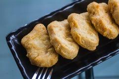 鸡块油煎了用在餐桌安置的西红柿酱 免版税库存图片