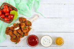 鸡块 油炸酥脆肉片断,在用不同的调味汁的纸在一张白色木桌上 库存图片