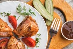鸡大腿烤了,蕃茄、黄瓜和调味汁在木背景 免版税库存图片