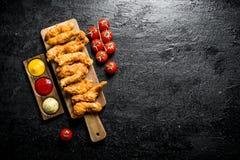 鸡小条用西红柿和不同的调味汁 免版税库存图片