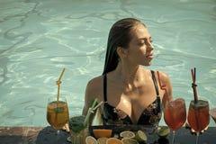 鸡尾酒和性感的女孩水池的 库存照片
