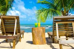 鸡尾酒和椅子在美丽的海滩 免版税库存照片