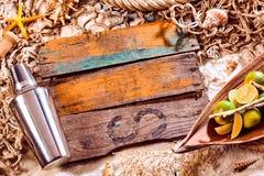 鸡尾酒搅拌器、石灰和木头板条在海滩 库存图片