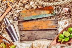鸡尾酒搅拌器、石灰和木头板条在海滩 免版税图库摄影