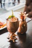 鸡尾酒服务在有盘的铜菠萝杯子里面在背景中 库存图片