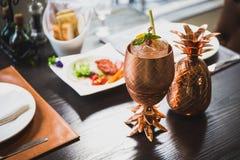 鸡尾酒服务在有盘的铜菠萝杯子里面在背景中 免版税库存图片