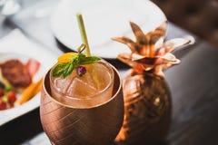 鸡尾酒服务在有盘的铜菠萝杯子里面在背景中 图库摄影