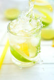 鸡尾酒柠檬和石灰在一块玻璃用水飞溅 库存图片