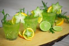鸡尾酒概念-三个在木头的绿色鸡尾酒standink,装饰用桔子、阳桃、石灰和迷迭香 当事人准备好 库存图片