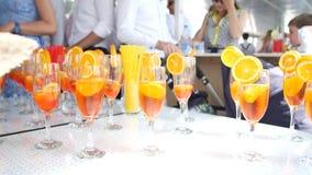 鸡尾酒用柠檬和桔子在玻璃 在a的鸡尾酒会 影视素材