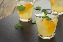 鸡尾酒 橙汁用薄菏和冰在土气木桌上 图库摄影