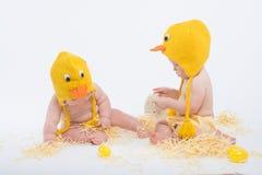 鸡服装的两个婴孩用黄色鸡蛋和干草 免版税图库摄影