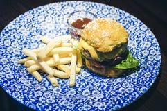 鸡汉堡包、油炸物和调味汁在蓝色板材在餐馆 库存图片