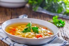 鸡汤 去骨汤用在白色碗的面条红萝卜和荷兰芹 库存图片