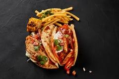 鸡法加它用烤葱和甜椒和服务用面粉玉米粉薄烙饼、玉米烤的和炸薯条  免版税库存照片