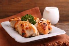 鸡烘烤了用在一块白色板材的香料 免版税图库摄影