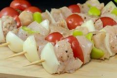 鸡烤肉串用蕃茄、葱和青椒在木头 免版税库存照片