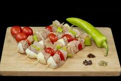 鸡烤肉串用蕃茄、葱和青椒在木头 库存照片