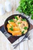 鸡用在一乳脂状的souce的蘑菇用在一个黑金属碗的油煎的白薯在木背景 健康 库存图片