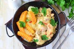 鸡用在一乳脂状的souce的蘑菇用在一个黑金属碗的油煎的白薯在木背景 健康 库存照片