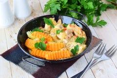 鸡用在一乳脂状的souce的蘑菇用在一个黑金属碗的油煎的白薯在木背景 健康 免版税库存图片