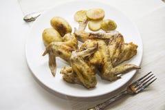 鸡翼和被烘烤的土豆 免版税库存照片