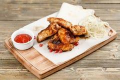 鸡翼格栅 服务在一张土气桌上的一个木板 烧烤店菜单,一系列的照片  库存图片
