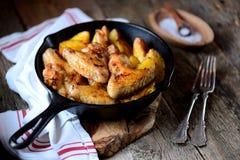 鸡翼烘烤了用在香料和芳香草本-蓬蒿、迷迭香、莳萝和大蒜的土豆在铸铁煎锅 图库摄影