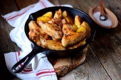 鸡翼烘烤了用在香料和芳香草本-蓬蒿、迷迭香、莳萝和大蒜的土豆在铸铁煎锅 库存照片