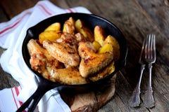 鸡翼烘烤了用在香料和芳香草本-蓬蒿、迷迭香、莳萝和大蒜的土豆在铸铁煎锅 免版税库存照片