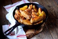 鸡翼烘烤了用在香料和芳香草本-蓬蒿、迷迭香、莳萝和大蒜的土豆在铸铁煎锅 库存图片