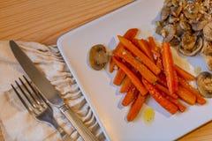 鸡肉、切的红萝卜和蘑菇 油煎的红萝卜 免版税库存照片
