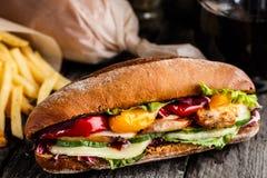 鸡肉三明治、油炸物和杯苏打 免版税库存照片