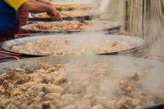 鸡肉在大平底锅蒸准备巨型肉菜饭 免版税库存照片