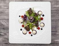 鸡肝用芳香抚人的调味汁沙拉,开胃菜 热的鸡肝沙拉用在板材特写镜头的莴苣 免版税库存照片