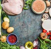鸡胸脯、红色小扁豆、新鲜蔬菜和各种各样的成份烹调的在土气背景,顶视图,框架 库存照片
