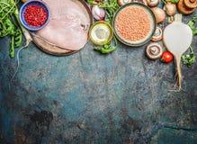 鸡胸脯、红色小扁豆、新鲜蔬菜和各种各样的成份烹调的在土气背景,顶视图 水平的边界 免版税库存图片