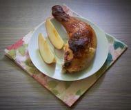 鸡腿用在桌上的苹果 免版税库存图片