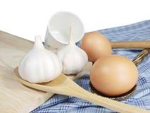 鸡蛋、大蒜、白色杯子和木匙子在蓝色织品 免版税图库摄影
