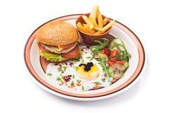 鸡蛋、汉堡和炸薯条在白色隔绝的板材 图库摄影