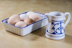 鸡蛋、牛奶和水罐在厨房用桌上 厨房用桌用食物 图库摄影