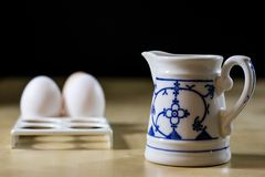 鸡蛋、牛奶和水罐在厨房用桌上 厨房用桌用食物 免版税库存照片