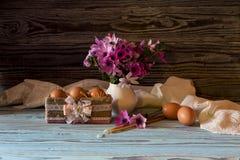 鸡蛋、狂放的银莲花属花束和教会蜡烛 免版税库存照片